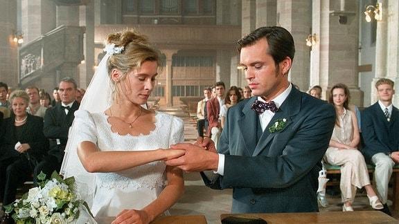 Thomas Noack (Ole Puppe) steht mit Sophia Baumann (Jeanette Arndt) vor dem Altar und steckt ihr einen Ring um den Finger.