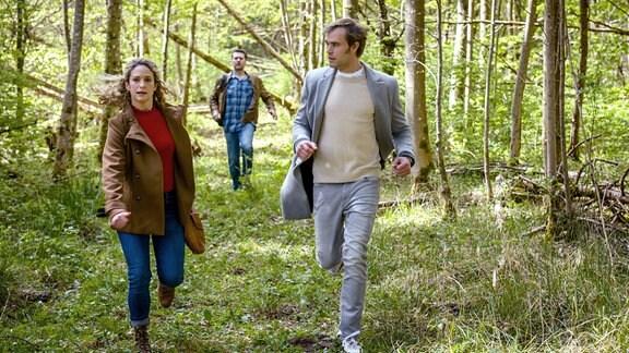 Franzi (Léa Wegmann, l.) und Steffen (Christopher Reinhardt, r.) fühlen sich verfolgt und flüchten panisch vor einem Spaziergänger (Komparse, M.).