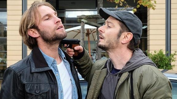 Felix Sonntag (Jochen Matschke) wird von Max Hellmann (Michael Baral) mit einer Pistole am Hals bedroht.