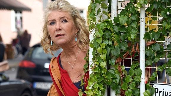 Fanny Steininger (Jutta Speidel) versteckt sich hinter einem Tor und beobachtet das Werkstattgelände.