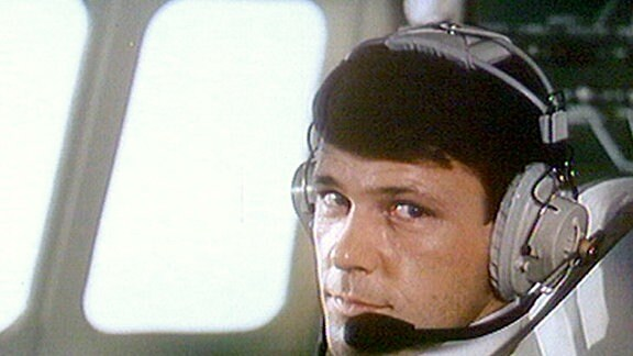 Walter Plathe in der Rolle als Paul Mittelstedt mit Kopfhörern im Cockpit.