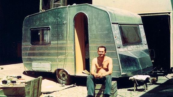 Bernhard Bräuner sitzt vor seinem selbst gebauten Wohnwagen.