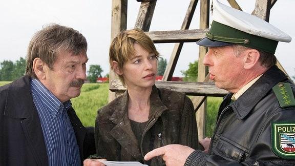Schneider (Wolfgang Winkler, links) und Adermann (Dieter Brandecker, rechts) haben Glück. Die Jägerin (Bettina Kurth, Mitte) erkennt mit Hilfe der gezeigten Fotos den Wagentyp wieder.