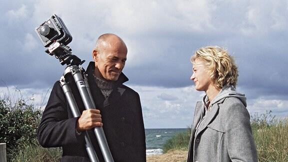 Ein Mann mit Kamera und einen Frau am Strand.