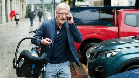 Anton (Ernst Stötzner) setzt auf Multitasking: den Kunden am Ohr und sein Baby am Arm.