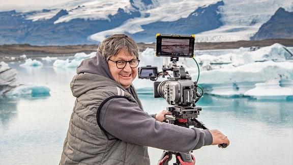Thomas Junker steht vor einem der Gletscherseen auf den isländischen Inseln.