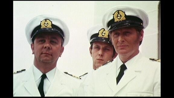 Drei Männer in Schiffsuniform blicken verschwörerisch in eine Richtung.