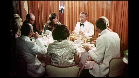 Männer und Frauen in Abendgarderobe sitzen um einen Tisch herum.