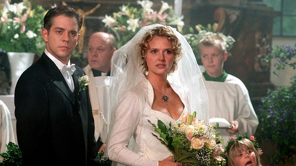 Lena Stern (Katharina Böhm) und Dr. Jörg Klein (Florian Fitz) stehen schon vor dem Altar der kleinen Dorfkirche, als die Tür aufgerissen und die Hochzeitszeremonie gestört wird.