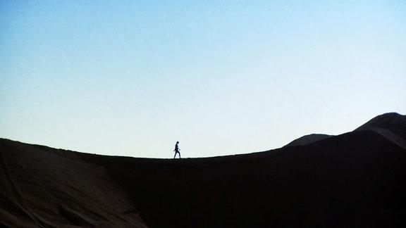 Anja (Lena Krimmel) wandert durch die karge Landschaft.
