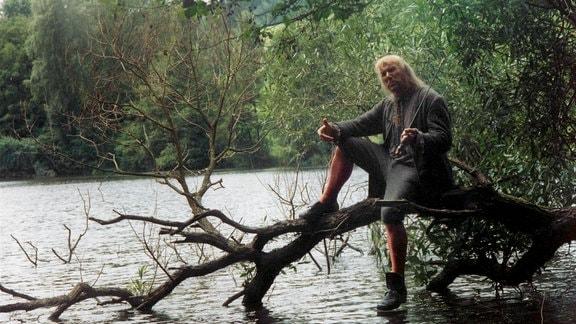 Baron - Wassergeist - (Jindrich Bonaventura) sitzt auf einem größeren ins Wasser reichenden Ast.