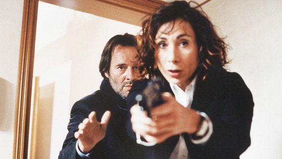 Signora Baresi (Andrea Eckert) zielt mit einer Pistole; Commissario Brunetti (Uwe Kockisch) i hintergrund.
