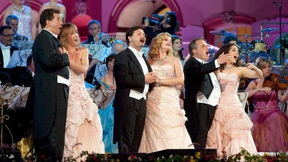 Drei Sängerinnen und drei Sänger auf einer Bühne