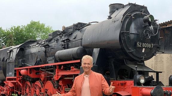 Olaf Berger vor einer normalspurigen Dampflok der Baureihe 52 außerhalb des Pressnitztals.