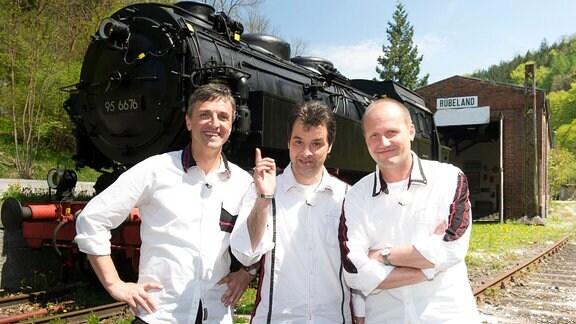 De Randfichten (V.l.: Lauti, Rups, Michel) vor einer in Harz eingetzten Dampflok der Baureihe 95.