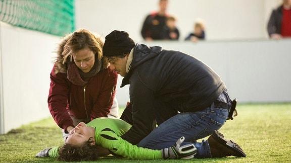 Esther Baumann (Katharina Marie Schubert) und Frank Baumann (Carlo Ljubek) sind zu Hannes Baumann (Mikke Rasch) auf den Platz geeilt. Frank will ihm hoch helfen, doch Hannes ist benommen.