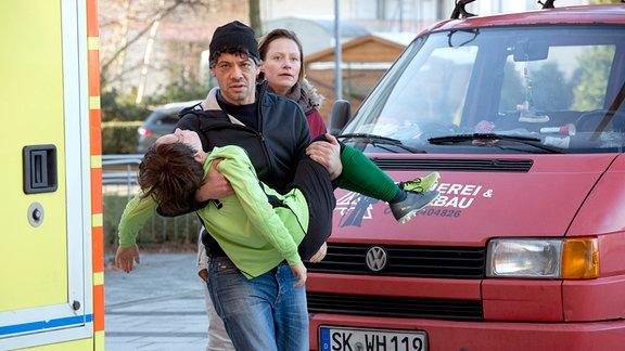 Frank Baumann (Carlo Ljubek) trägt Hannes Baumann (Mikke Rasch) in die Notaufnahme, gefolgt von seiner Ex-Frau Esther Baumann (Katharina Marie Schubert).