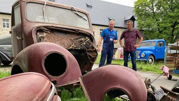 "Jens Scheunert und Bernd Schulze neben diversen Bauteilen eines ""Framo""."