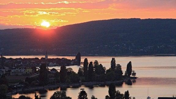 Die Sonne geht hinter den Bergen am Bodensee unter.