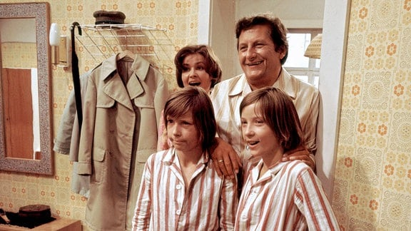 Die Zwillinge Kalle (Ralf Lemcke) und Kulle (Rolf Lemke, r.) stehen mit ihrer Mutter (Helga Labudda),und ihrem Vater (Erik S. Klein) in einem Zimmer. Sie tragen Schlafanzüge und lachen allesamt.
