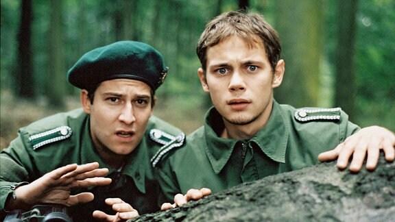 Paul Claussen (Antonio Wannek, re.) und sein Freund Konrad (Nils Bruno Schmidt) blicken über einen Findling in Richtung Kamera. Beide sind unformiert; sie scheinen Unerwartetes zu sehen.