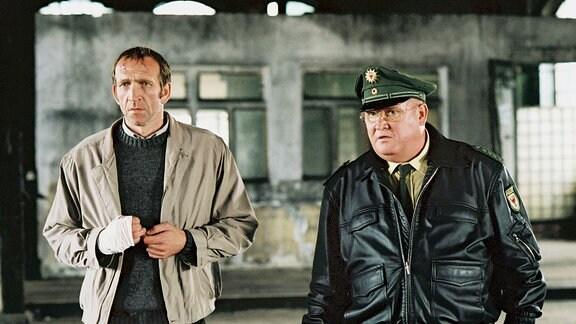 Revierpolizist Krause (Horst Krause) mit dem Tatverdächtigen Claussen (Jochen Nickel) in einem Raum, der wie eine Gr0ßgarage wirkt.