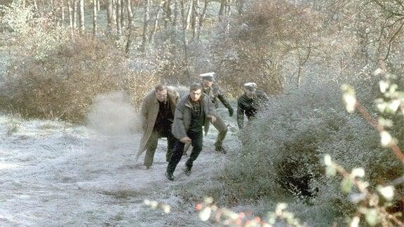 Die Kommissare Schmücke (Jaecki Schwarz) und Schneider (Wolfgang Winkler) laufen gemeisam mit zwei unformierten Polizisten geduckt durch einen herbstlichen Wald.