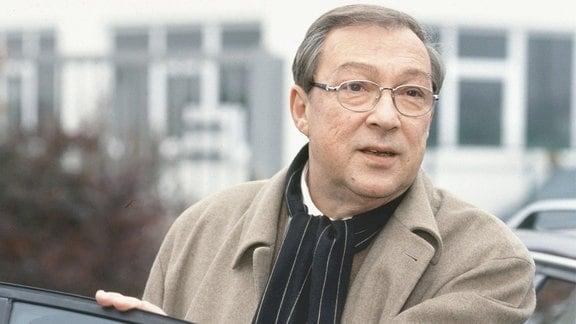 Kommissar Schmücke (Jaecki Schwarz) hinter einer geöffneten Autotür.
