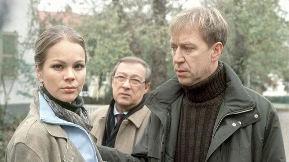 Kommissar Schmücke (Jaecki Schwarz) steht hinter Karl Wolter (Oliver Stritzel, r.) und dessen Stieftochter Carola (Angela Sandritter), die beide in die Kamera blicken.