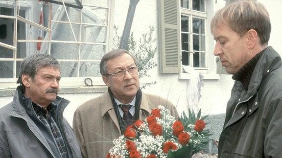 Die  Kommissare Schmücke (Jaecki Schwarz, Mitte) und Schneider (Wolfgang Winkler, l.) sprechen mit  Karl Wolter (Oliver Strizel) , der einen  Rosenstrauß in der Hand hält