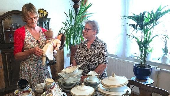 Die Schwestern im Wohnzimmer von Ina Schwarz, die nicht weit vom Elternhaus entfernt wohnt. Die zwei haben sich das gute Geschirr und auch die Puppensammlung der Eltern und Großeltern untereinander aufgeteilt. In den Dingen stecken allerhand Erinnerungen…