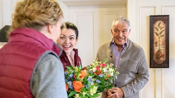 Maja (Christina Arends, l.) und Shirin (Merve Çakır, M.) sind begeistert, dass André (Joachim Lätsch, r.) einen von Majas Hüten kaufen will.