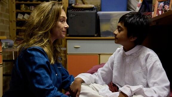 Sandy (Zayn Baig) sitzt im Lotussitz auf seinem Bett und meditiert, während Charlotte (Aglaia Szyszkowitz) ihm versucht die Regeln im Haus zu erklären.