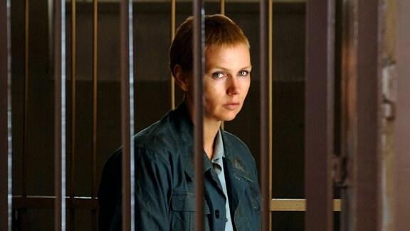 Sara (Veronica Ferres)  blickt durch Gitter.