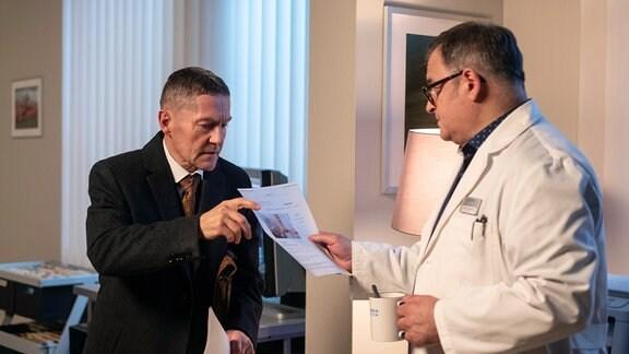 """Dr. Kaminski (Udo Schenk, li.) druckt mitten in der Nacht im Ärztezimmer Unterlagen aus. Hans-Peter Brenner (Michael Trischan, re.) entdeckt, dass es sich um Pflegedienste handelt und will ihm seine Hilfe anbieten, doch Kaminski lehnt """"dankend"""" ab."""