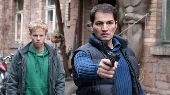 Ohne Vorwarnung schießt Maik Canavar (Bülent Sharif, rechts) auf Schmücke. René Scheffler (Martin Wißner, links) verhindert es nicht.