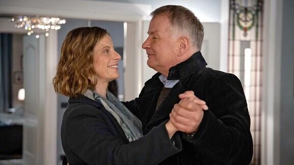 Katja Brücker (Julia Jäger) fragt Roland Heilmann (Thomas Rühmann) tanzen in einem Wohnraum ohne Zusachauer.