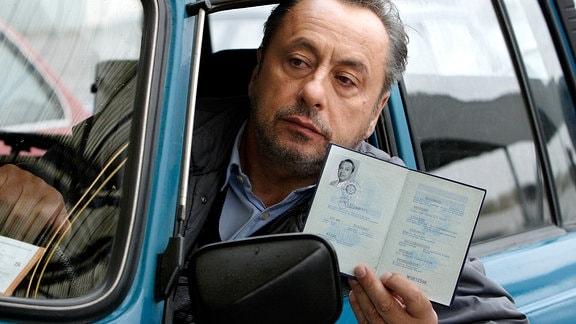 Stephan Busemann (Wolfgang Stumph) zeigt aus dem Fenster eines PkW seinen  Personalausweis.