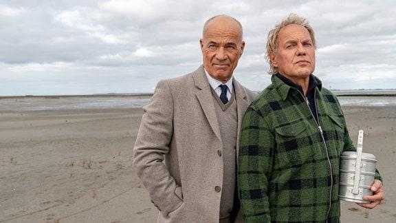 Zwei Männer stehen am Strand, ein Mann hält eine Urne in seinem Arm.