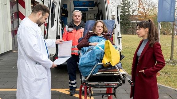 Drei Personen stehen hinter einem Krankenwagen. Zwischen ihnen steht eine fahrbare Krankentrage, au der eine Frau liegt.