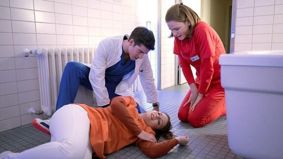 Maxi ( Leonie Rainer, M.) ist auf der Toilette zusammengebrochen. Ben (Philipp Danne, l.) und Louisa (Llewellyn Reichman, r.) wollen wissen, was passiert ist.