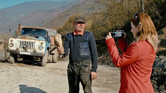 Dariko filmt einen Mann, der eine Eule in der Hand hält.