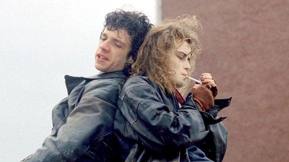 Alexander (Eduard Burza) und Sabine (Anja Kling)  sitzen Rücken an Rücken.