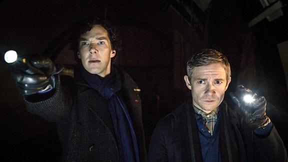 Sherlock Holmes (Benedict Cumberbatch, li.) und sein Assistent und Freund John Watson (Martin Freeman) suchen in einem stillgelegten Tunnel der Londoner U-Bahn nach einer Bombe.