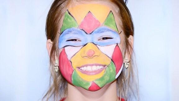 Ein Mädchen das im Gesicht geschminkt ist.