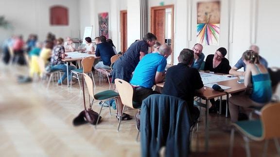 Menschen sitzen in Abritsgruppen zusammen