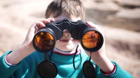 Ein Junge sieht durch ein Fernglas