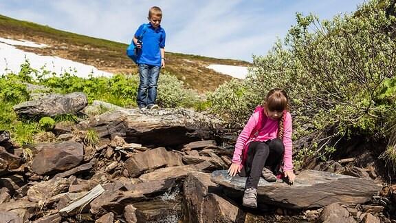 Ein Junge und ein Mädchen klettern zwischen Felsenbrocken