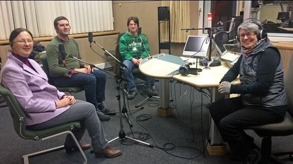 Vier Menschen sitzen in einem Rundfunkstudio vor Mikrofonen.
