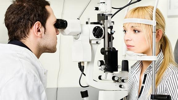 Eine Frau wird von einem Augenarzt untersucht